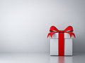 Gift box with red ribbon bow and empty white wall background abstract Royalty Free Stock Image