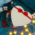A gift box in the shape of a heart with a red bow against the background of cozy turquoise blankets framed in decorative cotton,