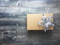 Gift box with a sliver bow holiday giving brown flower on stylish gray wood floor christmas Stock Image