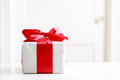 Gift box on table with red bow the white Royalty Free Stock Images