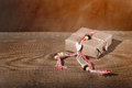 Gift box tied with decorative ribbon over wooden table backgroun