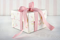 Gift box tied with pink ribbon floral pattern on white wooden background Royalty Free Stock Photography