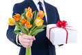 Gift box and tulip flowers in male hands isolated on white Stock Photos
