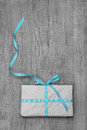 Gift box with turquoise striped ribbon on a wooden background giftbox Royalty Free Stock Photo