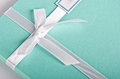 Gift box turquoise with white satin ribbon tied in a bowknot Royalty Free Stock Photo