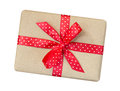 Gift box wrapped in brown recycled paper with red polka dot ribbon bow top view isolated on white background, clipping path
