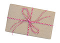 Gift box wrapped in brown recycled paper with red and white rope Royalty Free Stock Photo