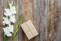 Gift box wrapped in craft paper near flower gladiolus on rustic wooden background top view copyspace