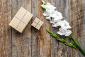 Gift box wrapped in craft paper near flower gladiolus on wooden background top view copyspace