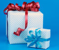 Gift boxes arrangement of two with ribbons and bows isolated on blue background Stock Images