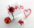 Gift boxes ball and candycane christmas still with white red heart on light background yop view Royalty Free Stock Photos