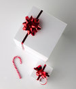 Gift boxes and candycane white with red bright bow on light grey background top view Royalty Free Stock Photography