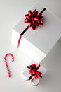 Gift boxes and stick of candycane white with red bright bow on light background top view Stock Photos