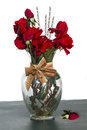 Gift of flowers glass vase with silk red roses and digitally placed bow and beaded stems Royalty Free Stock Photos