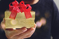 gift giving,man hand holding a gift box in a gesture of giving.blurred background,vintage effect Royalty Free Stock Photo