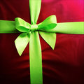 Gift green ribbon and bow on red paper Stock Image