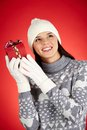 Gift guessing portrait of happy girl in winterwear holding giftbox by her ear Stock Images