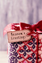 Gift with a label with the text seasons greetings