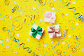 Gift or present box decorated colorful confetti, star, candy and streamer on yellow table top view. Flat lay style. Birthday. Royalty Free Stock Photo