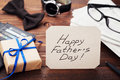 Gift or present box, newspaper, glasses, watch, bowtie and notes Happy Fathers Day on wooden table Royalty Free Stock Photo