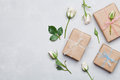 Gift or present box wrapped in kraft paper and rose flower on gray table from above. Flat lay styling. Copy space for text. Royalty Free Stock Photo