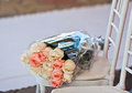 Gift rose bouquet in plastic wrapper on chair on wedding carpet left by one of guests a flowers lying white near white Royalty Free Stock Image