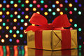 Gift wrapped present with a bow in front of a festive garland lights background soft focus Royalty Free Stock Image
