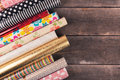 Gift wrapping paper rolls on wooden table with copy space