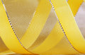 Gift yellow ribbon macro shot of a with golden textile background Stock Photos
