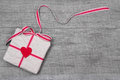 Giftbox wrapped in paper with a red heard on wood for valentine mother s day christmas or birthday Stock Photography