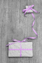 Giftboxes with purple striped ribbon on a grey wooden backround shabby background for voucher or coupon Royalty Free Stock Photo