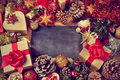 Gifts and christmas ornaments and a blank chalkboard Royalty Free Stock Photo