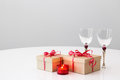 Gifts wineglasses and candlelight with red ribbons on a table Royalty Free Stock Photography