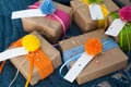 Gifts wrapped in kraft paper lie on a knitted rug. Royalty Free Stock Photo