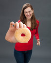 Giggling young woman grabbing a donut as junk food temptation Royalty Free Stock Photo