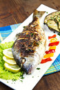 Gilt head sea bream on plate with lemon salad and grill grilled grilled vegetables Stock Photo
