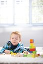 Ginger-haired toddler playing with cubes smiling Royalty Free Stock Photos