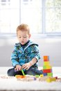 Ginger haired toddler playing on floor with building cubes Royalty Free Stock Photo