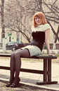Ginger-haired woman sitting on a bench Stock Image