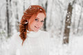 Ginger happy female in white sweater in winter forest. Snow december in park. Portrait. Christmas cute time.