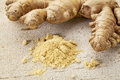 Ginger root and powder on a rustic white painted barn wood background Stock Photo