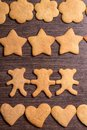 Gingerbread cookies bears in dance with hearts and stars on wooden background Royalty Free Stock Images