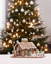 Gingerbread cottage house on real christmas tree background Stock Photos