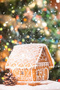 Gingerbread house over defocused lights of chrismtas decorated fir tree and snow Royalty Free Stock Image
