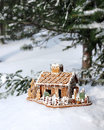 Gingerbread house in real winter snowy christmas forest background Royalty Free Stock Photo