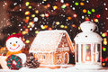 Gingerbread house on the snow snowman and candlestick Royalty Free Stock Image