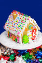 Gingerbread house with sprinkles gum drops and other candies sits on a cake stand with festive ribbons around the base Royalty Free Stock Photography