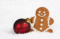 Gingerbread man and christmas ball cookie red ornament on snow background Royalty Free Stock Image