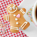Gingerbread man and coffee cup on table smiling Royalty Free Stock Photos