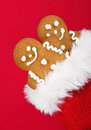 Gingerbread man cookies peeking out from christmas gift bag on red background Royalty Free Stock Images